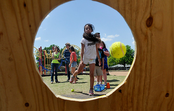 Bella Gonzales tosses a  ball during a game at the Hoover Elementary School block party Saturday. (Staff Photo by BILLY HEFTON)