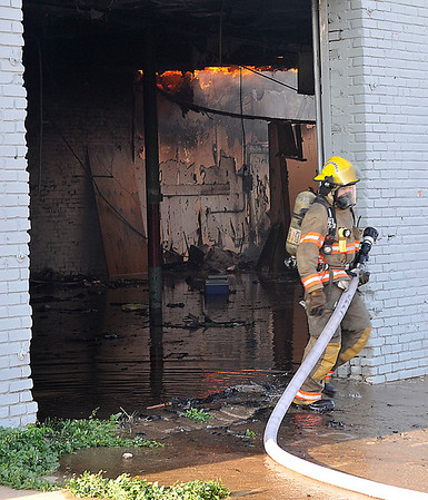 An Enid firefighter repositions himself while fighting a structure fire at Grand and Park Sunday. (Staff Photo by BILLY HEFTON)