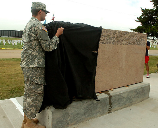 PFC. Corbin Johns unveils the names added to the Woodring Wall of Honor Memorial Day ceremonies Monday. (Staff Photo by BILLY HEFTON)
