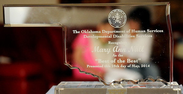 """Danielle Ioeger and Mary Ann Nall (back, from left) sit on a sofa near the """"Best of the Best"""" award presented to Nall by the Oklahoma Department of Human Services Developmental Disabilities Services at Nall's home Friday, May 30, 2014. Nall is a retired NORCE caretaker and adult companion for Ioeger for the past 27 years. (Staff Photo by BONNIE VCULEK)"""
