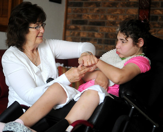 """Mary Ann Nall applies lotion to Danielle Ioeger's hands and arms in Nall's home Friday, May 30, 2014. Nall, who is a retired NORCE caretaker and adult companion for Ioeger 27 years, was recognized by the Department of Human Services as """"Best of the Best"""" Wednesday. (Staff Photo by BONNIE VCULEK)"""