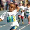 A young lady adjusts her hair as she sprints to the finish line during the 5th annual Be Fit Kids Buzz Run at Enid High School Saturday, May 17, 2014. (Staff Photo by BONNIE VCULEK)