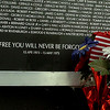 Flowers placed at the Vietnam Memorial Wall. (Staff Photo by BILLY HEFTON)