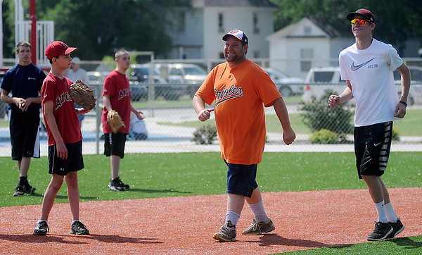 Orioles' Jeremy Clickner (center) runs the bases with his buddy as the Angels, Conner Ganz and Hunter Melvin (from left), play in the field during Miracle League games at AMBUCS ABC Park Saturday, May 31, 2014. (Staff Photo by BONNIE VCULEK)