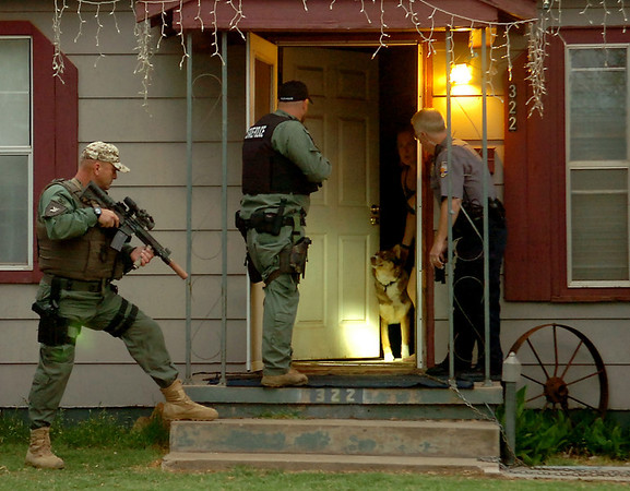 Law enforcement officers enter an Enid home during a large-scale drug sweep early Thursday, May 8, 2014. Oklahoma Bureau of Narcotics, Oklahoma Highway Patrol, Enid Police Department and Garfield County Sheriff Department were among the agencies involved in the sweep. (Staff Photo by BONNIE VCULEK)