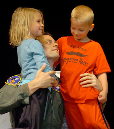 Lt. Col. Kevin Kohl (center) embraces his children, Grace and Austin, when he appears from under a giant science beaker during Wilson the Clown's magic show at Chisholm Elementary School Friday, May 2, 2014. Lt. Col. Kohl, who has been stationed in Iraq for six months, and his wife Melissa, planned the event with the help of Sara Dow and Dan Luskey. (Staff Photo by BONNIE VCULEK)