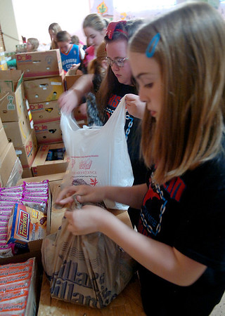 Katie Freeman (front right) and Kloee Black help other Chisholm Elementary School Crusaders package food at the Bethany United Methodist Church's Shepherd's Cupboard Wednesday, May 14, 2014. (Staff Photo by BONNIE VCULEK)