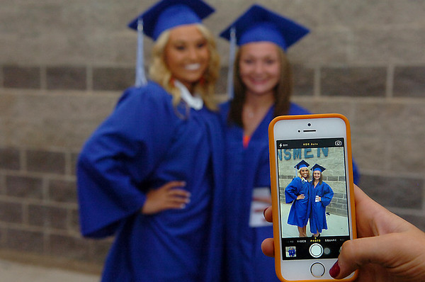 Brianna Burrow and Jaiden McAlister have a photo taken prior to the Enid High School Commencement Thursday at D. Bruce Selby Stadium. (Staff Photo by BILLY HEFTON)