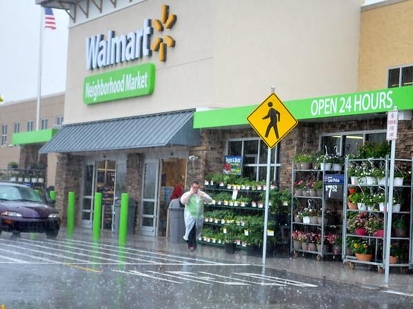 A Walmart Neighborhood Market associate dons rain gear as he assists customers during torrential rain Saturday, May 23, 2015. (Staff Photo by BONNIE VCULEK)
