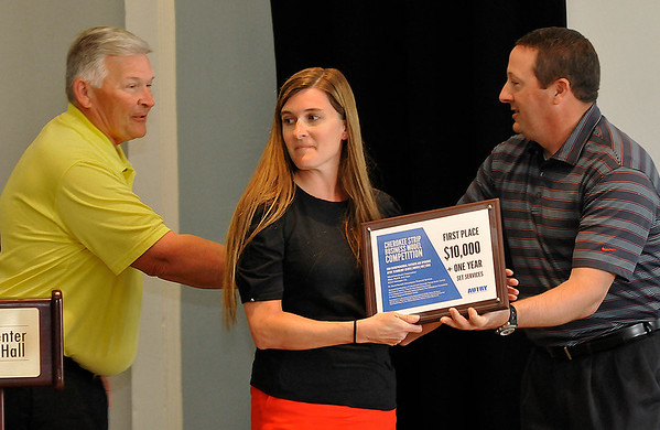 Darla Campbell and Bob Keiser (left) accept a plaque from Brian Gaddy for winning the Cherokee Strip Business Model Competition for their new business, Dandy's Donuts, Deli, Delights, during a luncheon Monday at Convention Hall. (Billy Hefton / Enid News & Eagle)