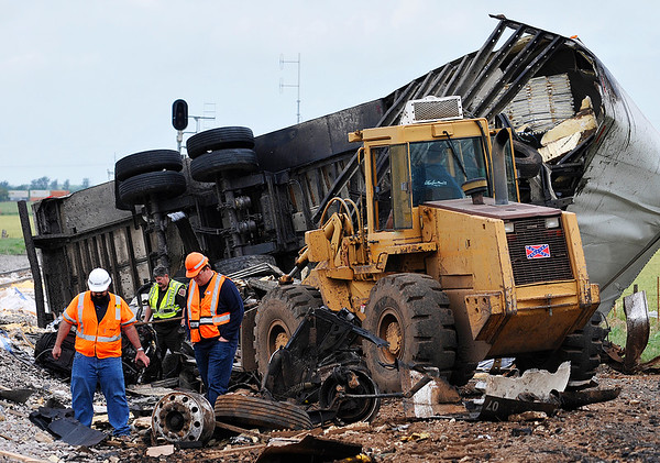 A front end loader is set to begin the clean up as BNSF workers and an Oklahoma highway patrolman look through the wreckage of a train vs tractor trailer fatality accident Monday May 9, 2016 at US 412 between 78th and 90th Streets. (Billy Hefton / Enid News & Eagle)
