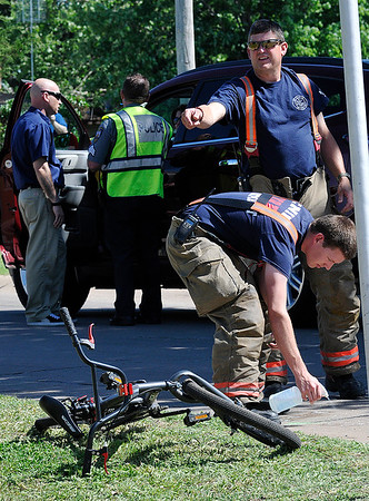 An Enid firefighter sprays disinfectant on blood at the scene of a vehicle vs bicycle accident Wednesday May 11, 2016 at the intersection of Cedar Ridge and Grennleaf. (Billy Hefton / Enid News & Eagle)