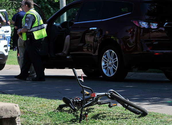 Enid emergency personnel work the scene of a vehicle vs bicycle accident Wednesday May 11, 2016 at the intersection of Cedar Ridge and Grennleaf. (Billy Hefton / Enid News & Eagle)