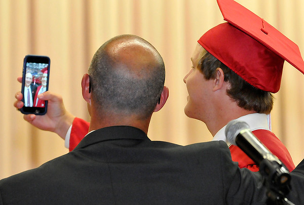 Cooper Savage takes a selfie with Chisholm High School principal, Shane Dent, after receiving his diploma cover during the Chisholm High School graduation Monday May 16, 2016. (Billy Hefton / Enid News & Eagle)