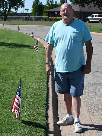 Don Von Hagel stands next to one of the 96 flags he placed along Gray Ridge Rd. in honor of Memorial Day. (Billy Hefton / Enid News & Eagle)