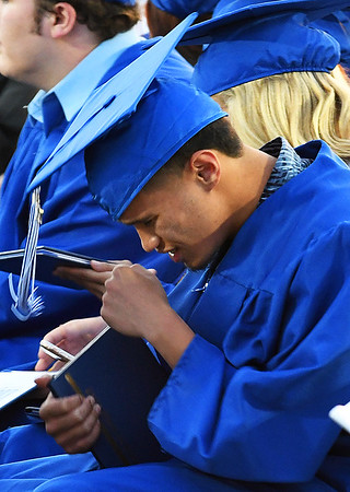 A member of the Enid High School Class of 2017 shows emotion after returning to his with with his diploma during commencement exercies Thursday May 25, 2017 at D. Bruce Selby Stadium. (Billy Hefton / Enid News & Eagle)