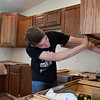Caleb Lively works on the cabinets in the house built by construction students at Autry Technology students. The house will be auctioned off May 18th. (Billy Hefton / Enid News & Eagle)