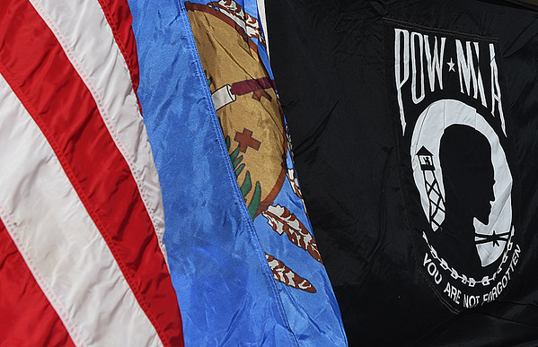 The American flag, the Oklahoma state flag and a POW MIA banner during Memorial Day ceremonies at the Woodring Wall of Honor Monday May 29, 2017. (Billy Hefton / Enid News & Eagle)