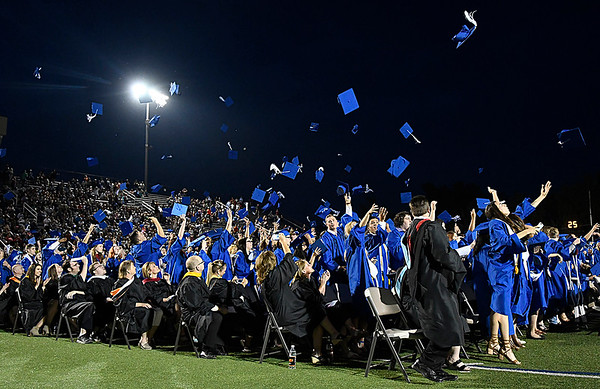 Members of the Enid High School Class of 2017 throw their hats into the air at the end of commencement exercies Thursday May 25, 2017 at D. Bruce Selby Stadium. (Billy Hefton / Enid News & Eagle)