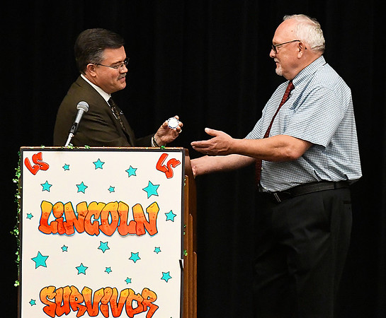 Enid schools superintendent, Dr. Darrell Floyd (left), presents retiring Lincoln Academy principal, Jarry Hillman, with a special district coin during Senior Appreciation Night Tuesday May 16, 2017. (Billy Hefton / Enid News & Eagle)