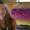 Catherine Freshley with one of her paintings in her studio May 25, 2017. (Billy Hefton / Enid News & Eagle)