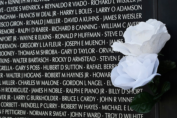 White roses next to a panel of names at the Vietnam Memorial Wall at the Woodring Wall of Honor and Veterans Park Monday May 28, 2018. (Billy Hefton / Enid News & Eagle)