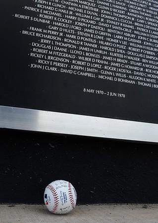 A baseball sits at the base of a panel of names at the Vietnam Memorial Wall at the Woodring Wall of Honor and Veterans Park Monday May 28, 2018. (Billy Hefton / Enid News & Eagle)