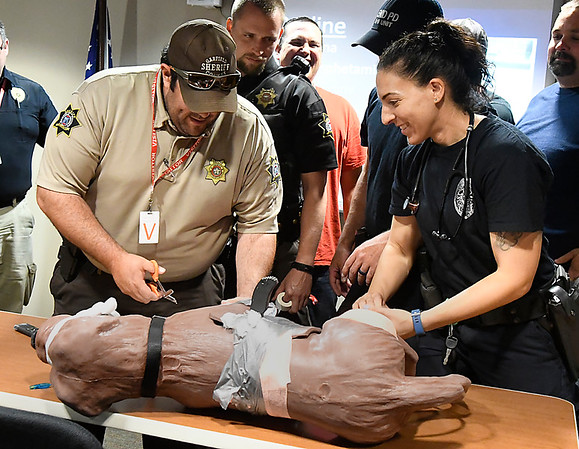Garfield County deputy, Darrell Beebe and Enid K-9 officer Michele James work on a dog dummie duriing a K-9 first aid class at the Enid Police Department Monday May 21, 2018. (Billy Hefton / Enid News & Eagle)