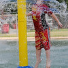 Aedan Dowell, son of Evi Dowell, leaps through cascading water at Champion Splash Pad Friday, August 23, 2013. Dowell frolicked in the water alone until Enid area school's dismissed for the weekend. (Staff Photo by BONNIE VCULEK)