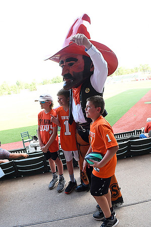 Oklahoma State mascot, Pistol Pete, poses for a photo with Wade Ewbank, Karsen Hennigh and Jase Hennigh during the Cowboy Caravan stop at David Allen Memorial Ballpark Monday May 14, 2018. (Billy Hefton / Enid News & Eagle)