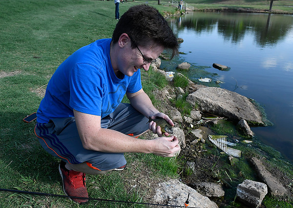 Robin Dodge works to free the hook from a fish at Meadowlake Park Tuesday May 15, 2018. Dodge released the fish back into the lake. (Billy Hefton / Enid News & Eagle)