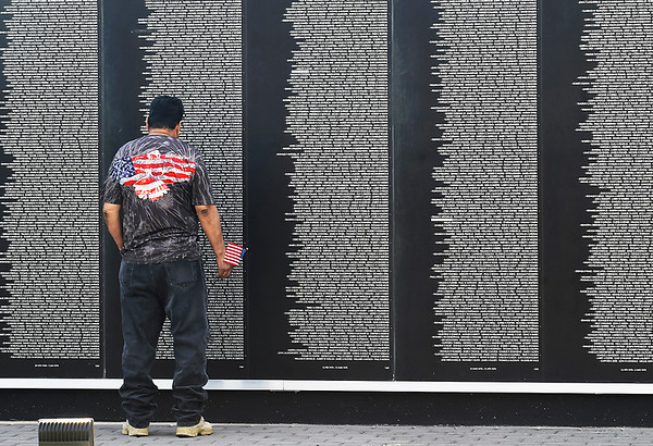 Frank Dominguez stands with a small American flag in front of the Vietnam Memorial Wall as he looks at the names of freinds he lost while serving in the Vietnam War as a teenager. (Billy Hefton / Enid News & Eagle)