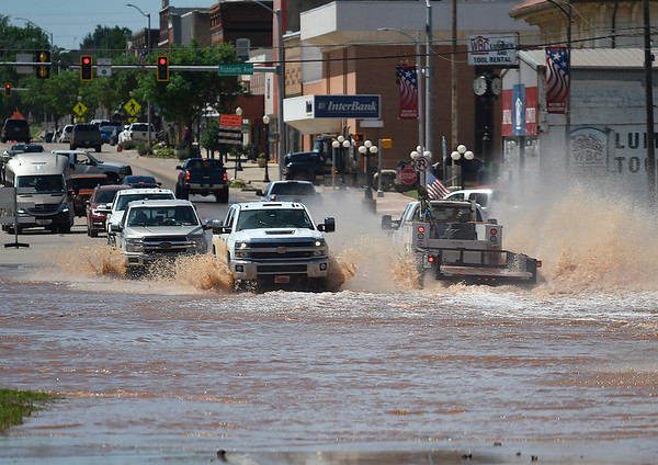 Traffic drives through flood water across U.S. 81 in downtown Kingfisher Tuesday May 21, 2019 prior to law enforcement diverting traffic. (Billy Hefton / Enid News & Eagle)