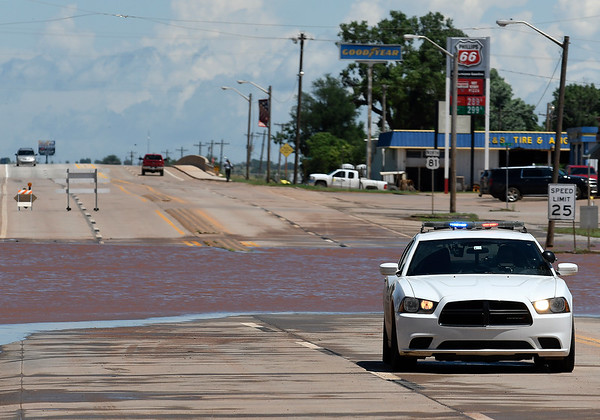 Kingfisher police block U.S. 81 near downtown Kingfisher Tuesday May 21, 2019 as flood water crosses the highway. (Billy Hefton / Enid News & Eagle)