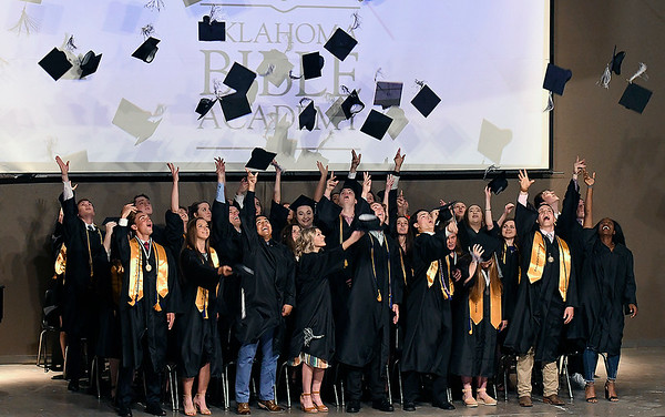 Oklahoma Bible Academy seniors toss their caps at the end of commencement exercises Friday May 24, 2019. (Billy Hefton / Enid News & Eagle)