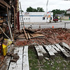 Tommy Farnsworth walks on the bricks that were the wall of his garage/workshop in Jet. The wall collapsed after it was struck by lightning Tuesday night. Farnsworth is offering free bricks to anyone who comes to pick them up. (Billy Hefton / Enid News & Eagle)