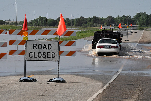 A car follows a truck through high water on U.S. 81 Wednesday afternoon May 22, 2019 between Medford and Pond Creek. The road was closed due to high water. (Billy Hefton / Enid News & Eagle)