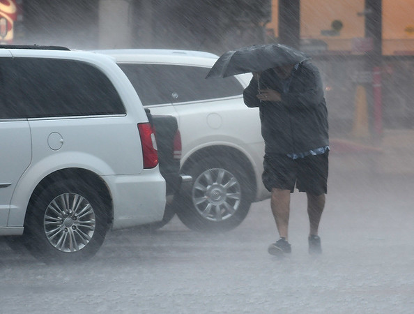 A man uses  a small umbrella as he crosses the Jumbos West parking lot Monday May 20, 2019. (Billy Hefton / Enid News & Eagle)