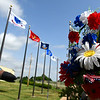 Memorial flowers hang on the fence at the Woodring Wall of Honor and Veterans Park Monday May 27, 2019. (Billy Hefton / Enid News & Eagle)