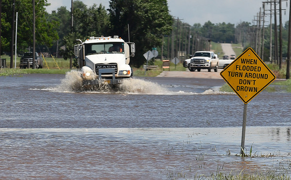 A commerical truck drives through flood water on 13th street in Kingfisher Tuesday May 21, 2019. (Billy Hefton / Enid News & Eagle)