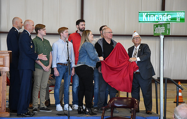 Enid mayor, George Pankonin, helps family members of Lt. Col. John Kincade unveil a street sign honoring the late airman during the Woodring Wall of Honor Memorial Day ceremony Monday, May 31, 2021. (Billy Hefton / Enid News & Eagle)