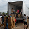 Volunteers from the Open Door Church and Calvary Baptist Church unload boxes of food and milk that were given away at the Calvary Baptist Church parking lot Wednesday, May 5, 2021. (Billy Hefton / Enid News & Eagle)