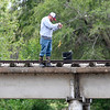A man catches a fish while fishing from the railroad bridge at Meadowlake Paek Wednesday, May 5, 2021. (Billy Hefton / Enid News & Eagle)