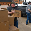 Ron Horner and Suzayne Horner hand out boxes of food and milk at the Calvary Baptist Church parking lot Wednesday, May 5, 2021. The food and milk was given away by the Open Door Church and Calvary Baptist Church. (Billy Hefton / Enid News & Eagle)