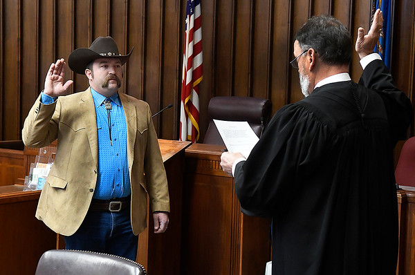 Cory Rink (left) takes the oath of office as Garfield County Sheriff from Judge Tom Newby Monday, January 4, 2021 at the Garfield County Courthouse. (Billy Hefton / Enid News & Eagle)
