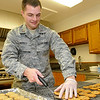 Lt. James Inkrott places cookies on trays to cool Tuesday as part of Operation Cookie Cutter. Volunteers bakes cookies to send to troops from Vance Air Force Base deployed overseas. (Staff Photo by BILLY HEFTON)