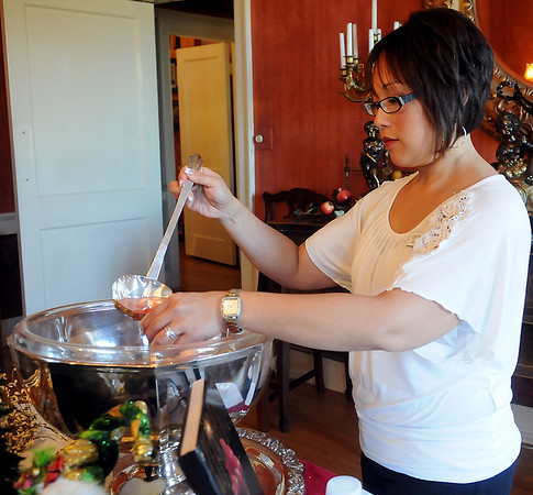 Angelica Berry serves a cup of Christmas Cranberry Punch Thursday during Junior Welfare League of Enid's Ninth Annual Cookbook Marketplace. (Staff Photo by BONNIE VCULEK)