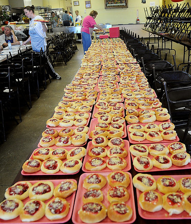 Fresh baked kolaches cover table tops at Our Daily Bread Saturday as the Ladies Auxiliary prepare 180 dozen of the sweet treats for their annual holiday fundraising sale. Popular flavors include cherry, apricot, pineapple, prune and poppyseed. (Staff Photo by BONNIE VCULEK)