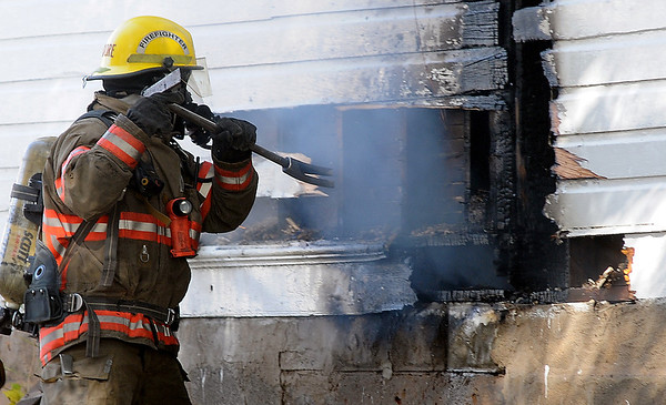 Enid firefighter Adrian Moore uses a pry bar to remove siding from a burning home at 414 E. Maple Friday. (Staff Photo by BONNIE VCULEK)