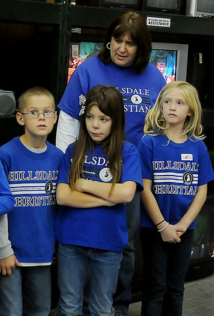 Gretchen Streck (top) and her second grade students (from left) Daniel Voth, Emily Corey and Alice Watkins wait for the beginning of their second performance at Hope Outreach Tuesday. Streck's class sang three songs at the Hope Outreach homeless shelter before entertaining customers at the organization's thrift shop. (Staff Photo by BONNIE VCULEK)